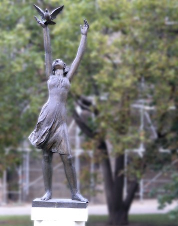 A beautiful statue in Berlin of a young woman releasing a dove