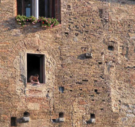 A young man looking out a window in Florence, Italy demonstrates the Rule of Thirds