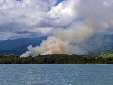 A large bush fire with the Finisterre Mountains in the background