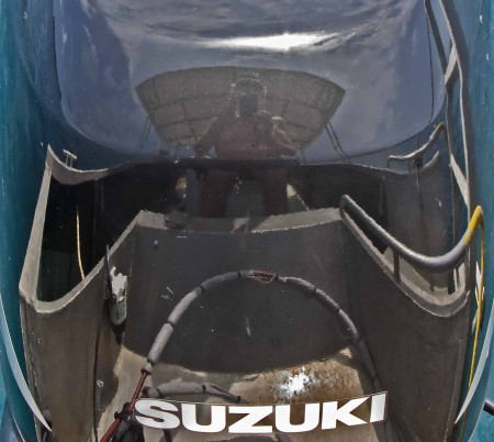 Photographer and boat reflected in the shiny cowl of the outboard motor