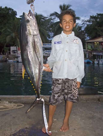 A happy little kid who caught a Yellowfin Tuna nearly as big as himself